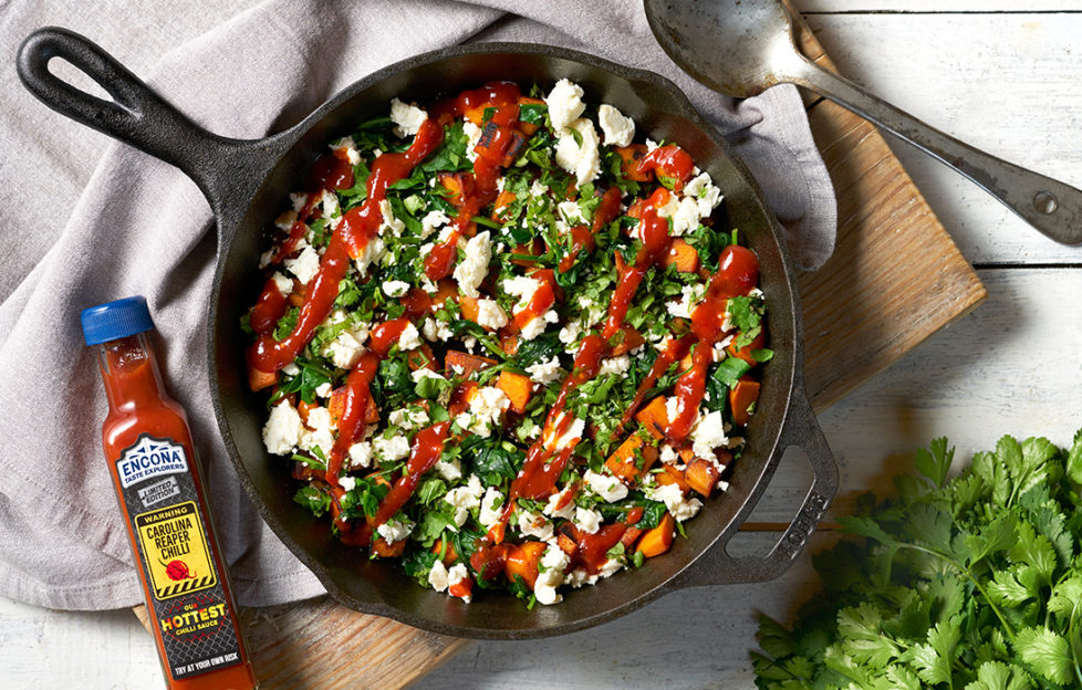 Cast iron frying pan with feta, spinach, sweet potato and drizzle of red chilli sauce
