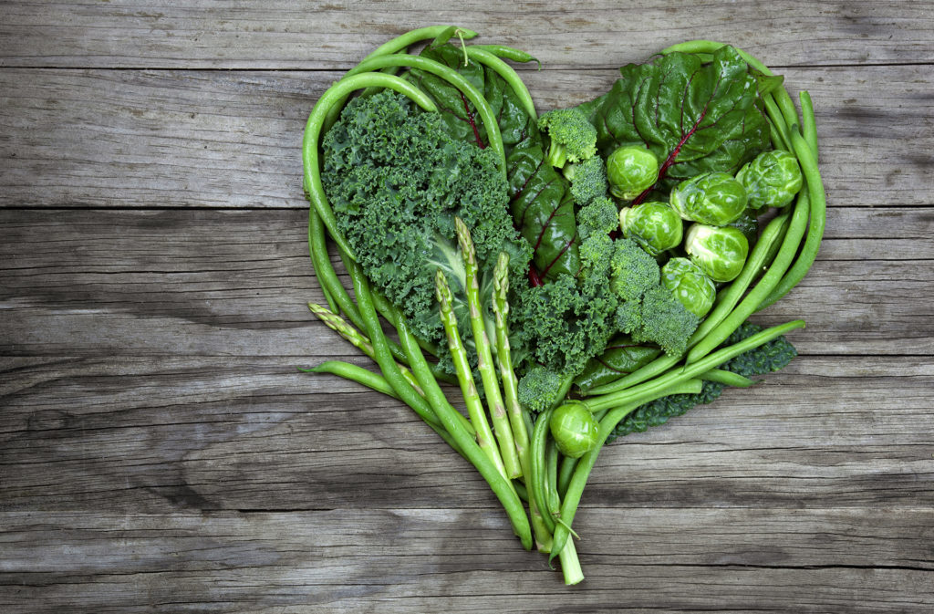 Green vegetables in a heart shape on an old wood background. Vegetables include various lettuce, kale, green beans, asparagus, brussel sprouts, and broccoli.