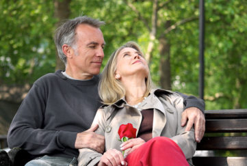 Loving mature couple sitting on park bench Pic: Istockphoto