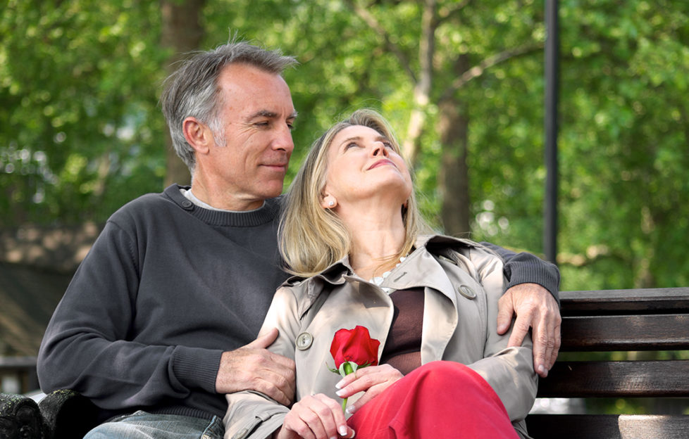 Loving mature couple sitting on park bench Pic: Istockphoto