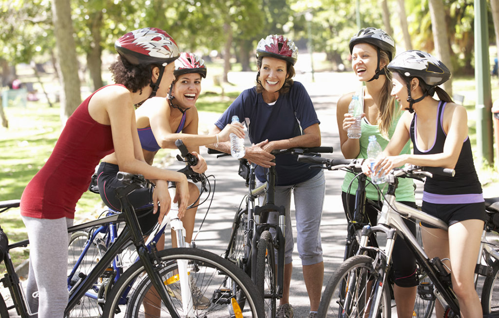 Group Of Women Resting During Cycle Ride Through Park Laughing And Drinking Water