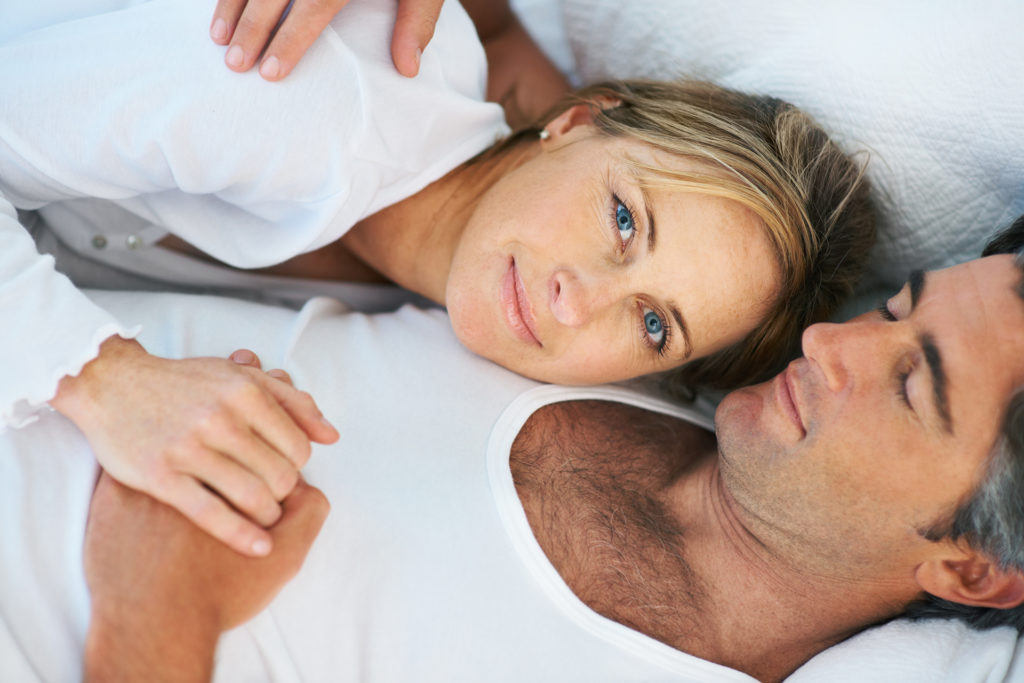 Happy mature couple lying in bed together