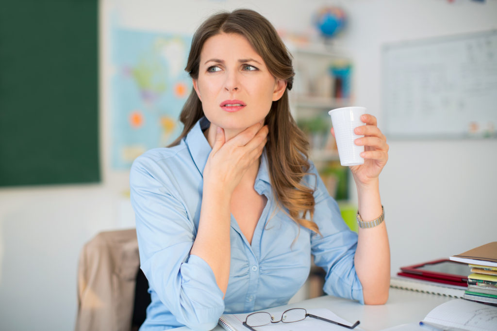Woman with a sore throat and water