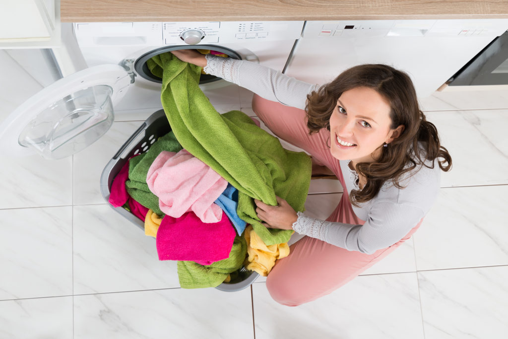 Woman Loading Clothes In Washer