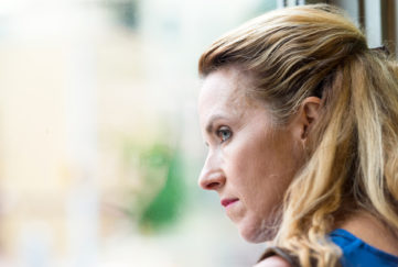 Pensive Mature blonde woman looking out of window