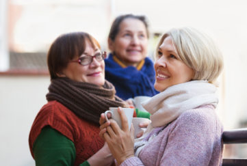 Senior female in warm clothes having cup of hot tea on terrace. Focus on blonde woman