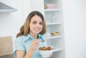 Cute woman holding a bowl with cereals while smiling at camera