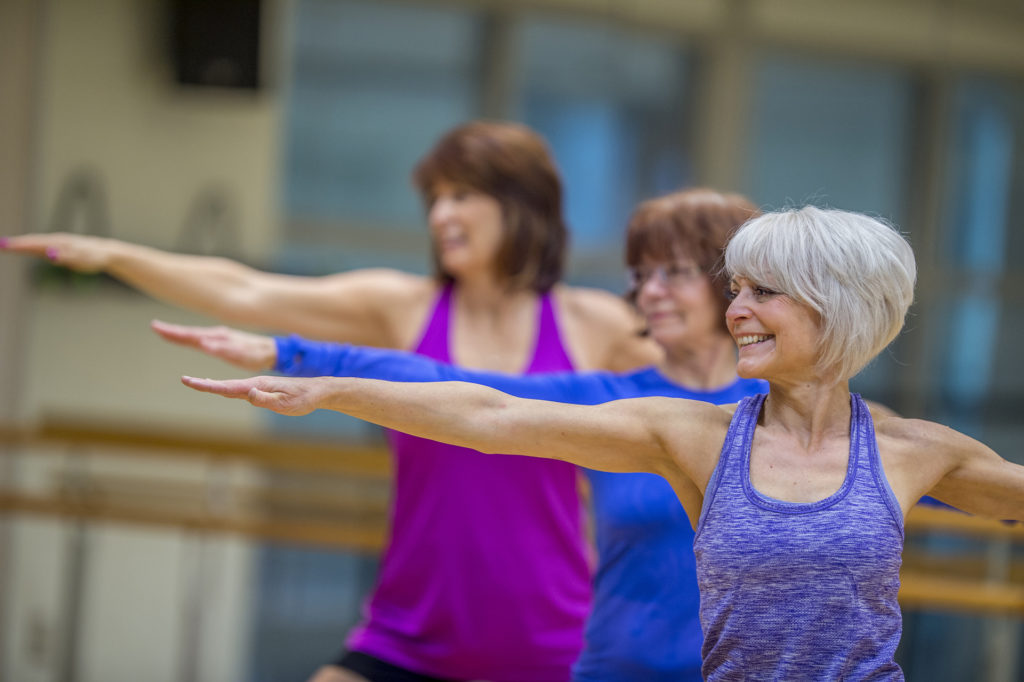 Three Caucasian senior women are indoors in a fitness center. They are wearing casual exercise clothing. They are standing and stretching their arms out while doing yoga. One woman is smiling in the foreground.