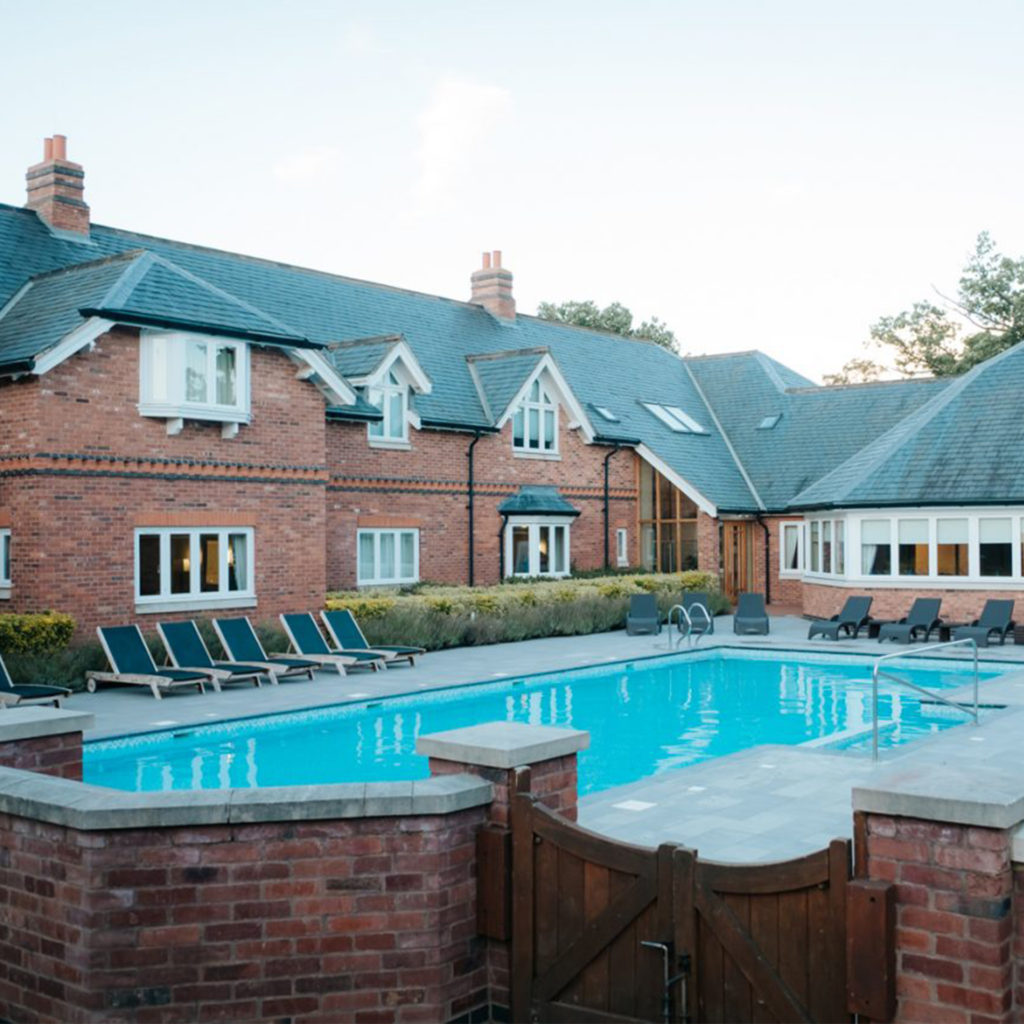 Red brick buildings and conservatory overlooking heated outdoor pool at Ardencote spa