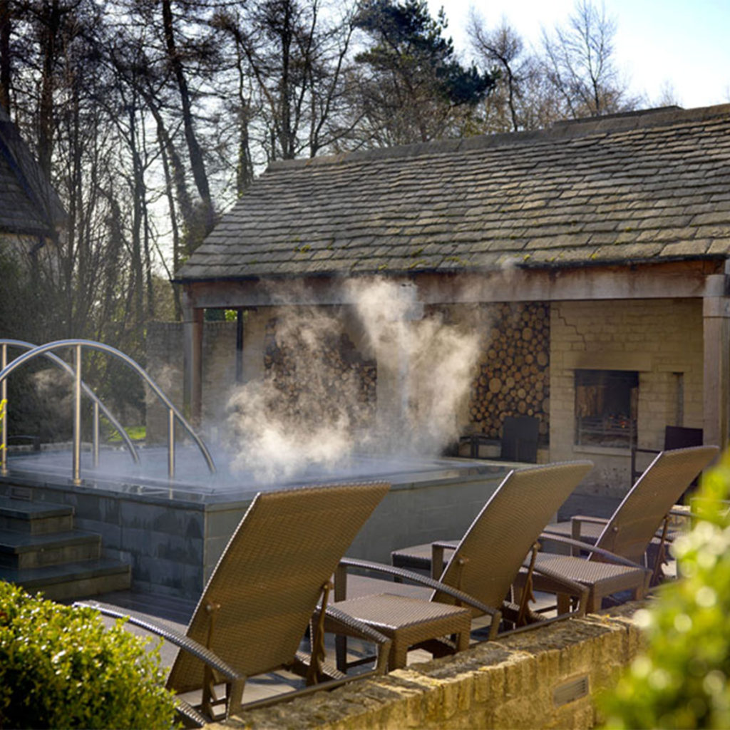Steaming outdoor hot tub, sun loungers and beautiful old woodshed at Calcot Manor