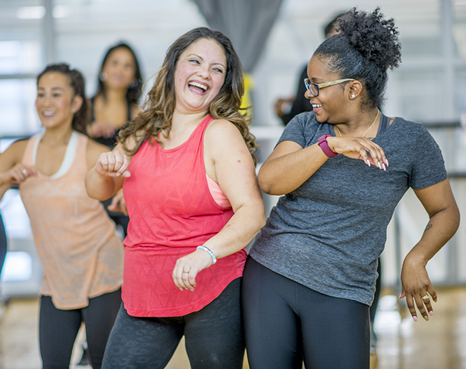 A multi-ethnic group of adult women are dancing in a fitness studio. They are wearing athletic clothes. Two women are laughing while dancing together.. Pic: istockphoto