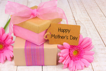 Handmade gift boxes with Happy Mother's Day tag and flowers on white wood Pic: Istockphoto