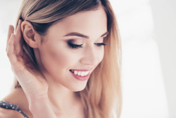 Pretty woman holding hair back from ear Pic: Istockphoto