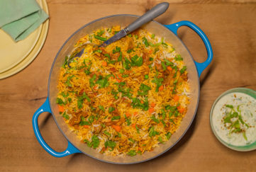 Blue casserole dish of chicken biryani with chopped coriander
