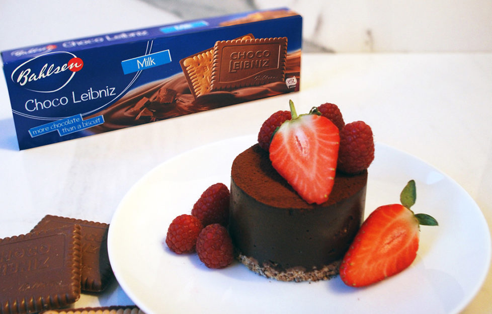 Rich chocolate tart decorated with strawberries and raspberries, with a packet of Bahlsen Choco Leibniz biscuits