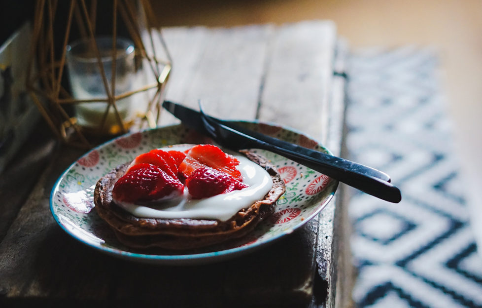 Chocolate pancake topped with yoghurt and stawberries