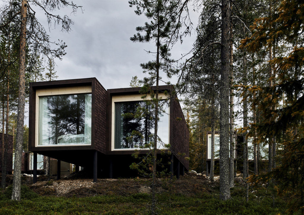 Modern building, looks like two cubes with a window fillimg the ends facing camera, surrounded by pine trees