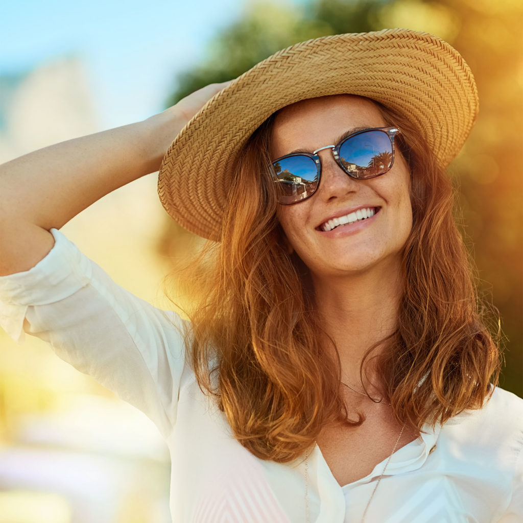 Auburn-haired woman in sunglasses, light shirt and floppy hat, enjoying a summer's day outdoors
