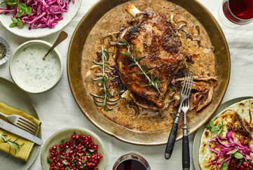 Roasted lamb in rich sauce with rosemary sprigs. Also glasses of red wine, pomegranate seeds, red cabbage and rosemary yogurt