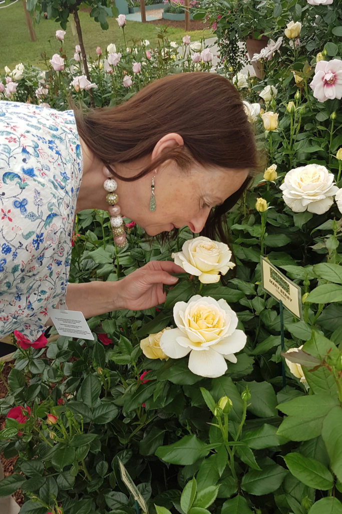 Woman bending down to smell roses