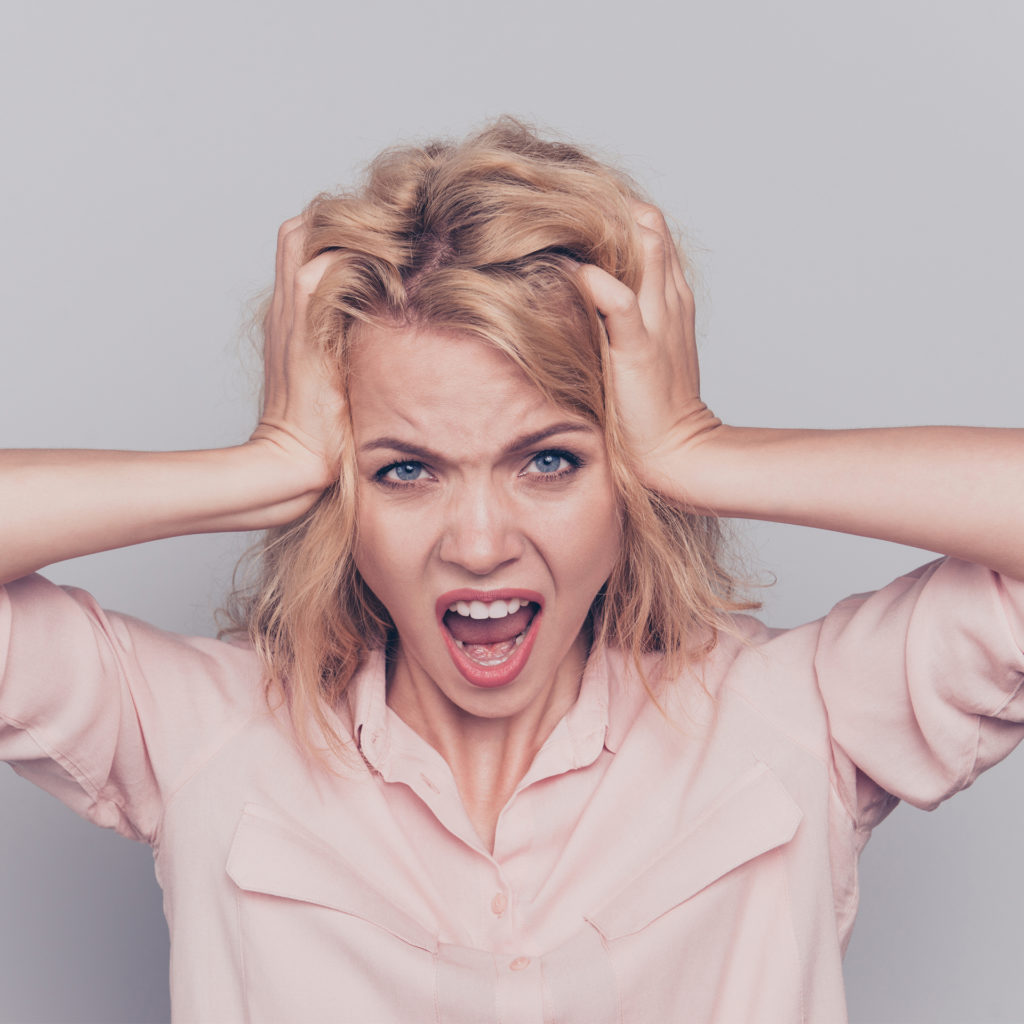 Blonde woman shouting in anger and frustration, hands to her head