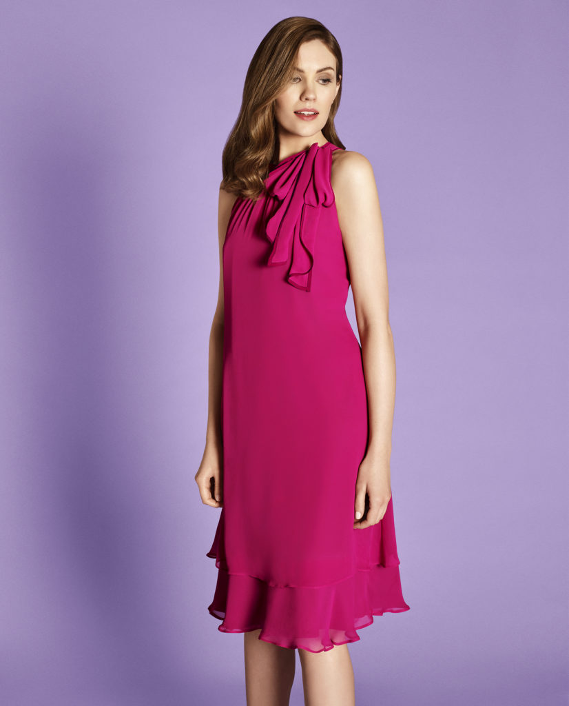 Woman in sleeveless cerise dress, two layered hem just below knee, soft pleated ruffle hanging from left shoulder