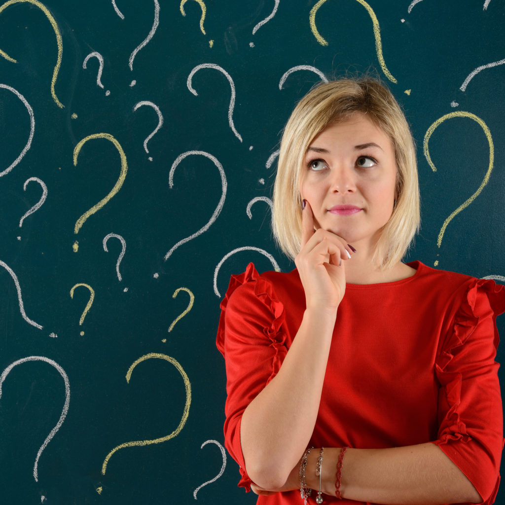 Woman in red dress looking thoughtful in front of blackboard covered in question marks