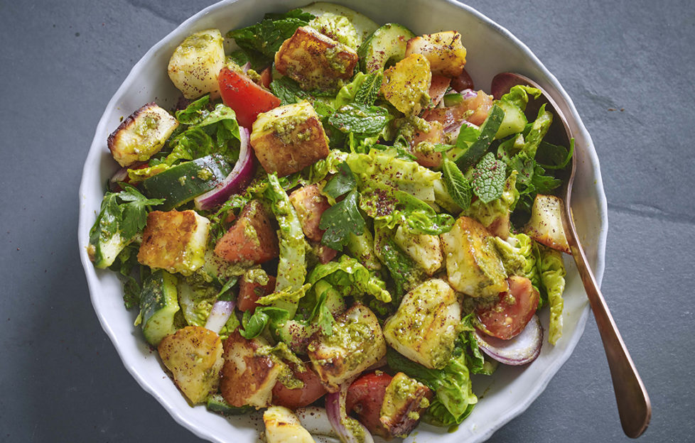 Bowl of halloumi salad with cubes of toasted cheese, cucumber, tomato, onion and tiny lettuce leaves