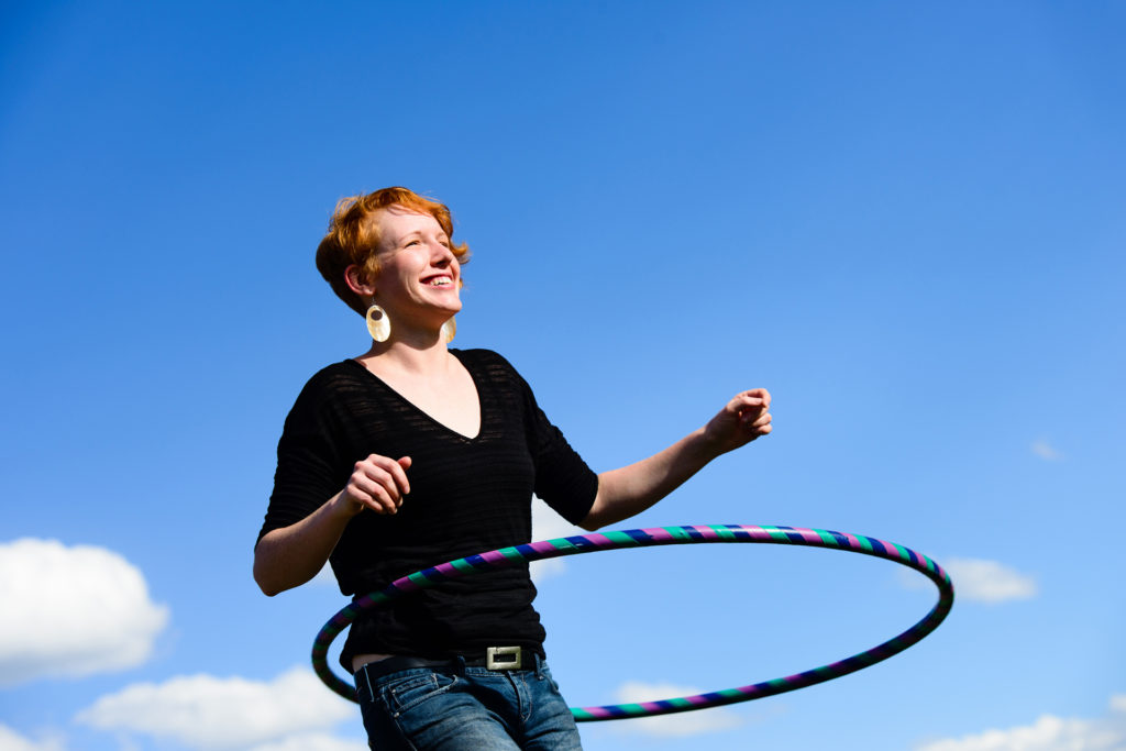 A red headed female outside playing with a hula hoop. Sky, clouds and trees in the background.