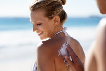 A smiling woman on the beach with someone applying sunscreen to her back