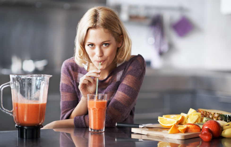 A young woman happily sipping on her homemade smoothie