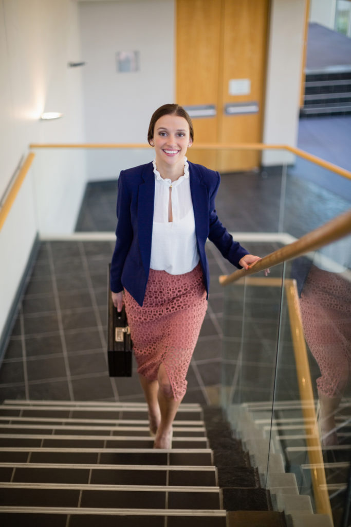 Portrait of a businesswoman carrying briefcase climbing steps at conference centre