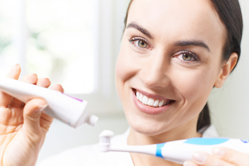 Woman Squeezing Toothpaste Onto Electric Toothbrush In Bathroom