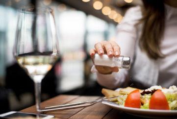 Woman adding salt to food in restaurant.