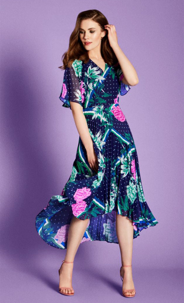 Brunette model in v neck floaty cap sleeve dress, navy with bright pink flowers and teal leaves, skirt of narrow pleats, hemline higher at the front
