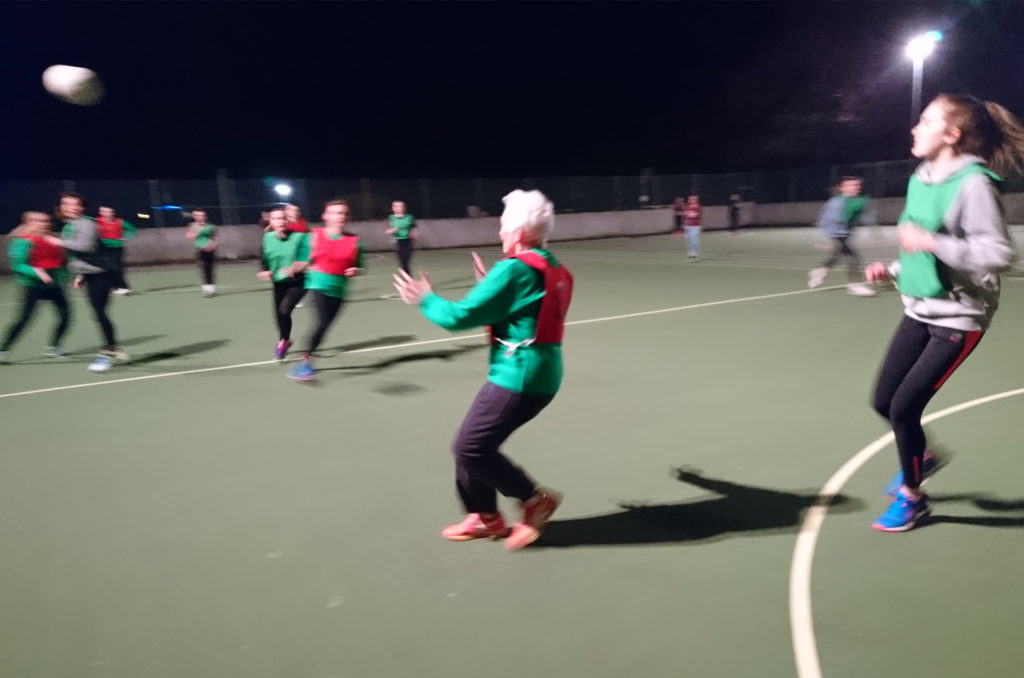 Elderly lady playing netball, about to catch the ball, other players in background