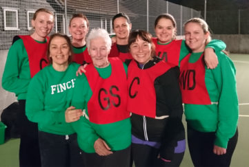80-year-old netballer Anne Wilby with fellow members of her netball team, in netball vests on a floodlit outdoor court