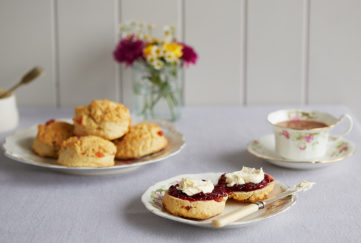 Plate of cherry scones, and another plate with a scone cut in half spread with jam and cream, also vase of flowers and teacup