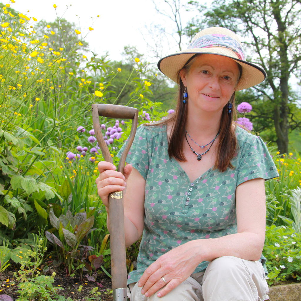 Gardening expert Susie White wearing sage green blouse, white trousers and straw hatkneeling by tall, thriving plants