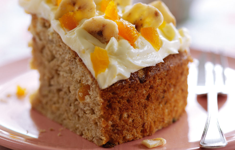 Slice of banana cake decorated with cream icing, banana chips and pieces of apricot