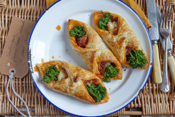 Three small puff pastry rolls, with bright green broccoli, Parma ham and melted cheese showing at each end