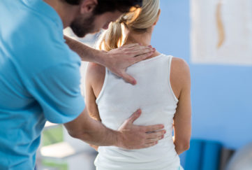 Male therapist treating woman's back, both standing
