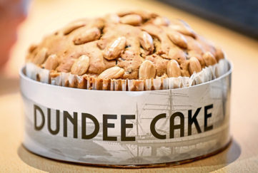 Freshly baked Dundee cake, golden brown topped with almonds, in a paper case