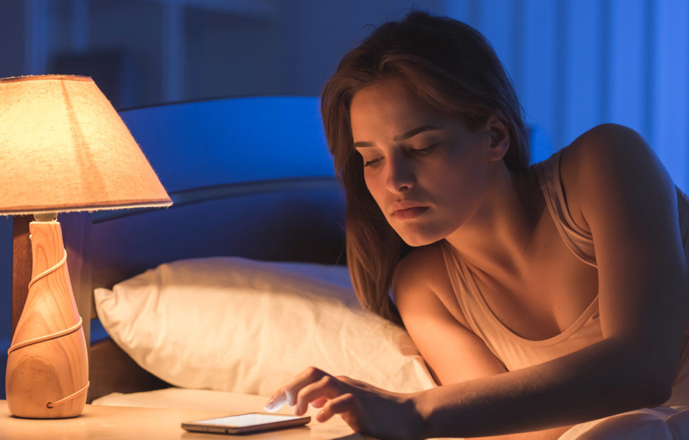 Woman in bed in night checking phone at bedside