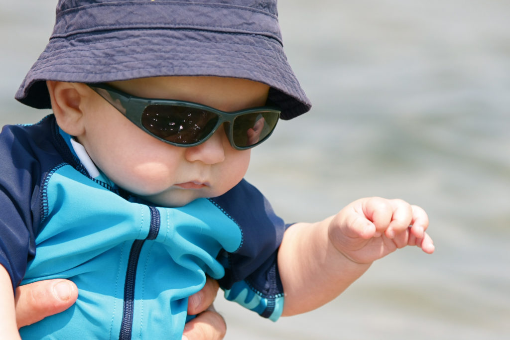 """""""A baby boy, wearing sunglasses and a sun hat, enjoys a day at the beach."""