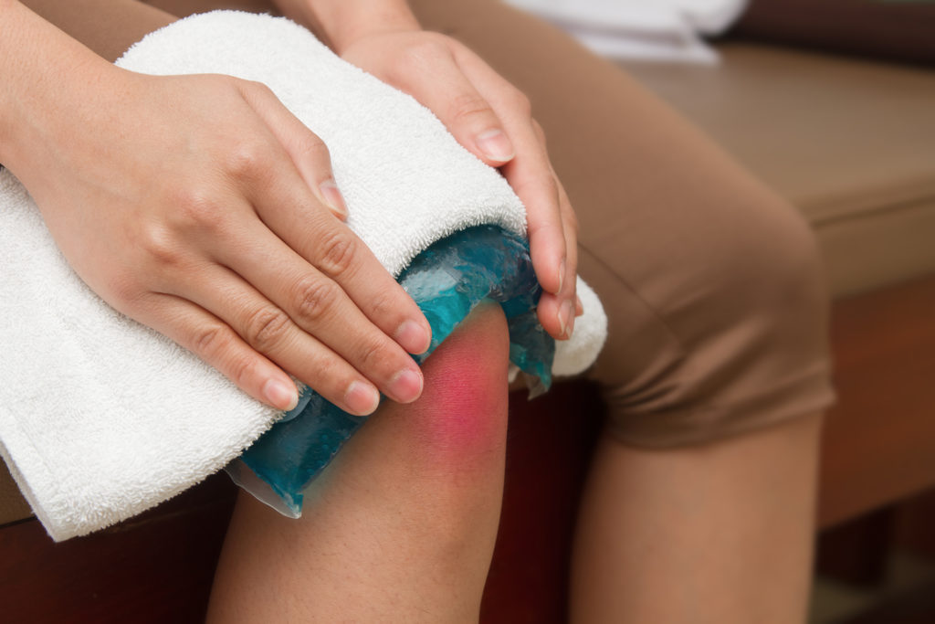 a woman applying cold pack on  swollen hurting knee after accident