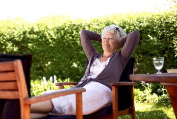 Senior woman sitting on a chair and taking a nap in backyard. Elder woman sleeping in backyard garden