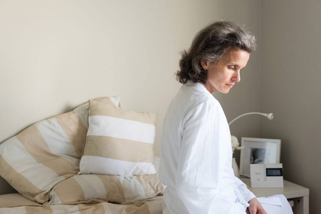 Middle aged woman sitting on bed