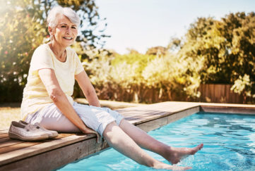 Lady dipping toes in pool looking happy Pic: Istockphoto