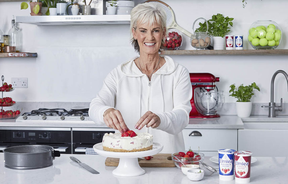 Judy Murray in kitchen, smiling, with strawberry cheesecake on worktop and plants, strawberries and jar of tennis balls on shelves behind